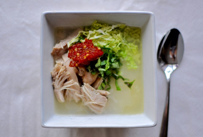 Chicken congee in a square bowl with garlic and chill paste