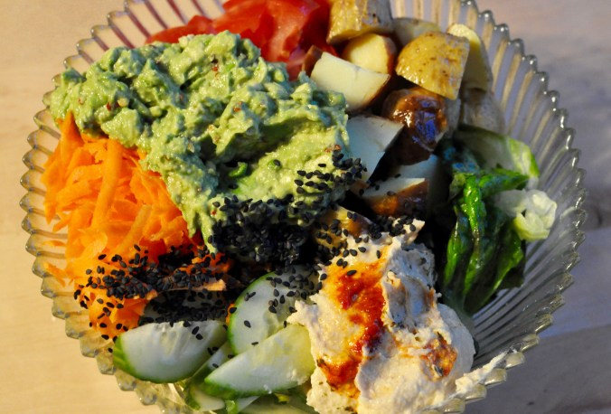 Salad with avocado, potato, shredded carrots, cucumbers, and tomato.