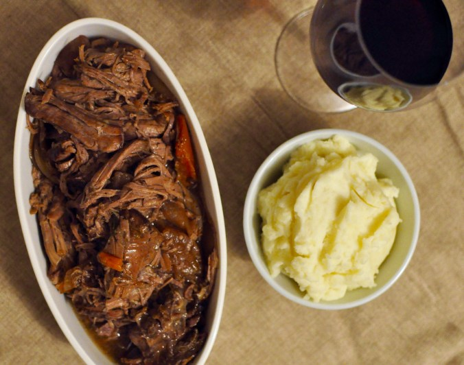 Pot roast in a narrow serving vessel with a glass of red wine and a small white bowl of mashed potatoes.