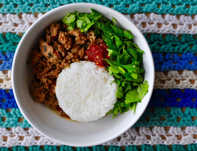 Round white bowl with white rice, minced pork, chili sauce, and fresh herbs.