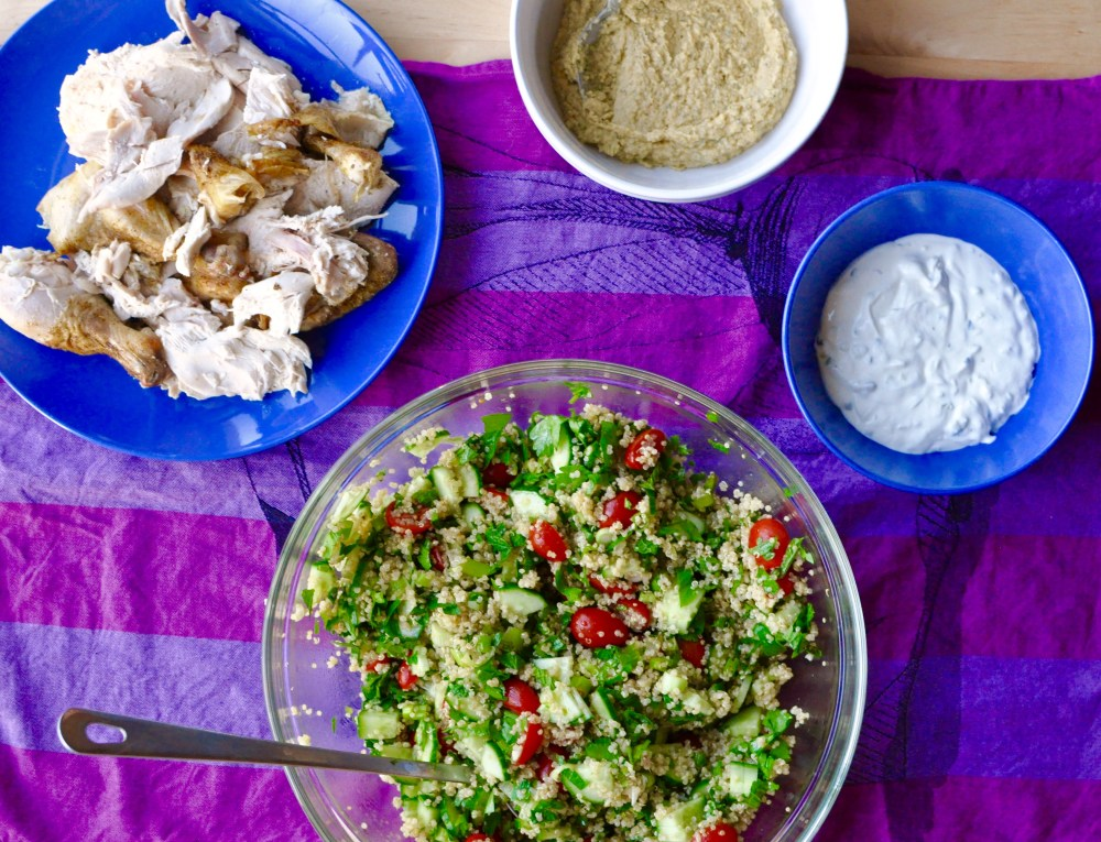 Roast chicken, tabouleh, hummus, and tzatziki arranged in serving dishes on a bright purple tablecloth
