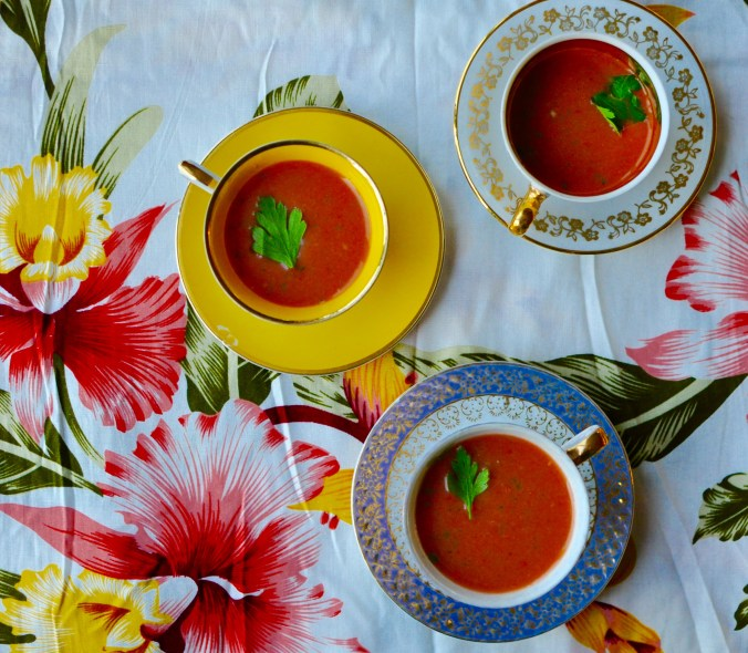 Colourful teacups on a flowered tablecloth, filled with pink watermelon gazpacho.