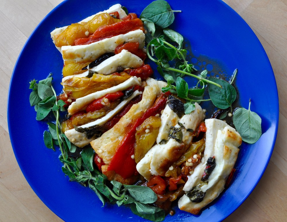 Slow roasted sweet peppers layered with slices of halloumi on a bright blue plate with decorative sprigs of halloumi cheese.