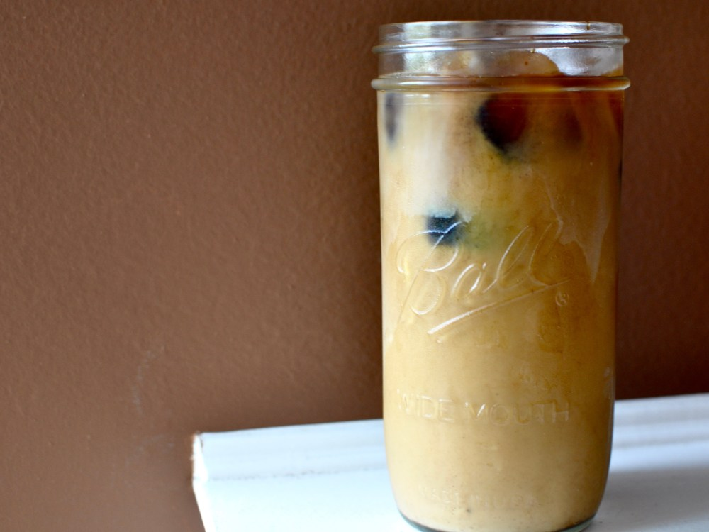 A Mason jar full of milky iced coffee against a burgundy background.