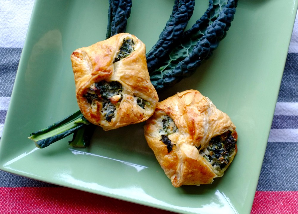 A pale green plate with 2 Kale and Ricotta Spinach Puff Pastries resting on top of 3 kale leaves.