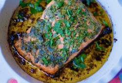 A round white baking dish that contains a fillet of baked trout in olive oil with herbs.