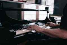 Man learning to play the piano and taking piano lessons.