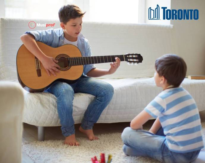 boy plays for his little brother. guitar lessons Toronto