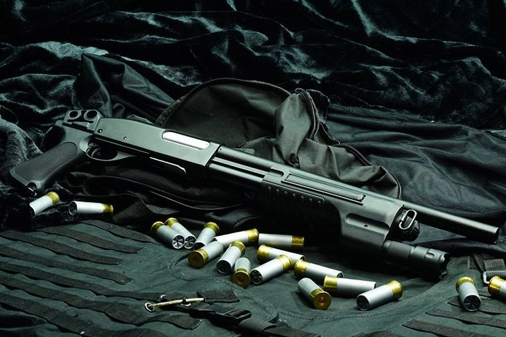 Shotgun and light set on black background and bullet