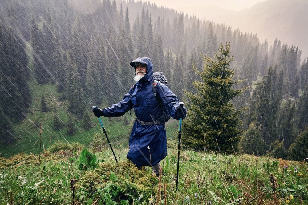 old hiker in blue rain jacket