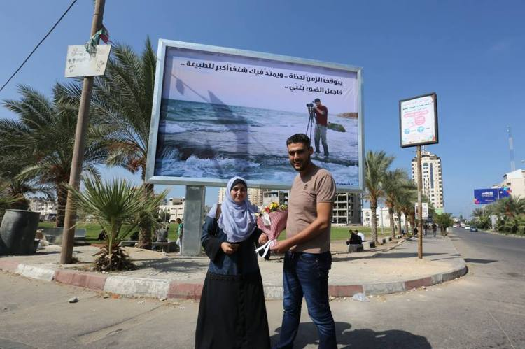 Samah Shamali, and Mahmoud Abu Hamda stand in front of the board where his picture was put