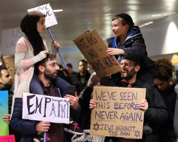 Meryem Yildirim, 7, left, sits on her father, Fatim, of Schaumburg, and Adin Bendat-Appell, 9, right, sits on his father, Rabbi Jordan Bendat-Appell, of Deerfield, during a protest on Monday, Jan. 30, 2017 at O'Hare International Airport in Chicago, Ill. (Nuccio DiNuzzo/Chicago Tribune/TNS)
