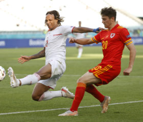 BAKU, AZERBAIJAN - JUNE 12: Daniel James of Wales crosses the ball whilst under pressure from Kevin Mbabu of Switzerland during the UEFA Euro 2020 Championship Group A match between Wales and Switzerland at the Baku Olympic Stadium on June 12, 2021 in Baku, Azerbaijan. (Photo by Valentin Ogirenko - Pool/Getty Images)
