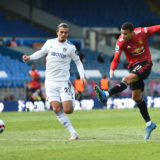 LEEDS, ENGLAND - APRIL 25: Mason Greenwood of Manchester United takes a shot whilst under pressure from Pascal Struijk of Leeds United during the Premier League match between Leeds United and Manchester United at Elland Road on April 25, 2021 in Leeds, England. Sporting stadiums around the UK remain under strict restrictions due to the Coronavirus Pandemic as Government social distancing laws prohibit fans inside venues resulting in games being played behind closed doors. (Photo by Peter Powell - Pool/Getty Images)