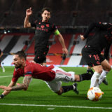 MANCHESTER, ENGLAND - FEBRUARY 25: Alex Telles of Manchester United is tackled by Mikel Oyarzabal of Real Sociedad and Andoni Gorosabel of Real Sociedad during the UEFA Europa League Round of 32 match between Manchester United and Real Sociedad at Old Trafford on February 25, 2021 in Manchester, England. Sporting stadiums around the UK remain under strict restrictions due to the Coronavirus Pandemic as Government social distancing laws prohibit fans inside venues resulting in games being played behind closed doors. (Photo by Laurence Griffiths/Getty Images)