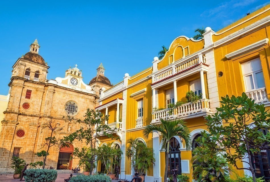 Church and yellow colonial building visible from San Pedro Claver plaza in historic Cartagena | 10 of the Most Colorful Cities in the World