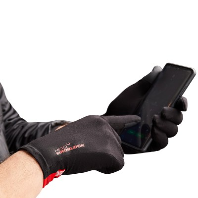 Photograph of two hands wearing the HeiQ Viroblock Antimicrobial black gloves, and using a mobile phone. The words HeiQ Viroblock are written small in red on the back of the glove. There is a red tag on the wrist of the glove that says, Swiss Tech Inside