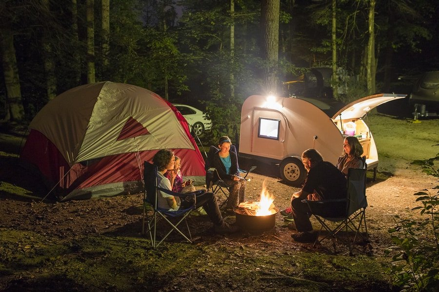 Family of five camping at night with campfire