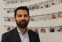 Бизнесмен Фарзад Голчин на фоне фотографий мигрантов, которым помогла найти работу в Швеции его компания. Фото: Валерий Поташов