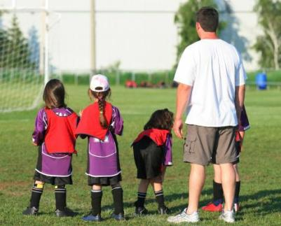 little girls playing soccer with coach.jpg