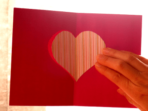 Paper cut out card, held up against the light to see through the design on the reverse side