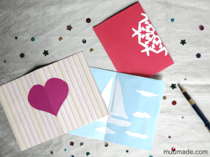 Paper cut-out cards: a heart, a sail boat, and a snowflake