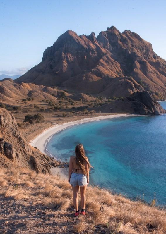 Komodon kansallispuisto | Tyttö kukkulan huipulla ranta- ja vuoristomaiseman edessä.