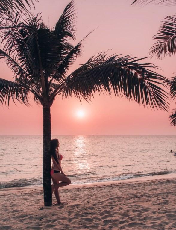 Millainen matkailija olen | Tyttö nojaa palmuun auringonlaskussa.