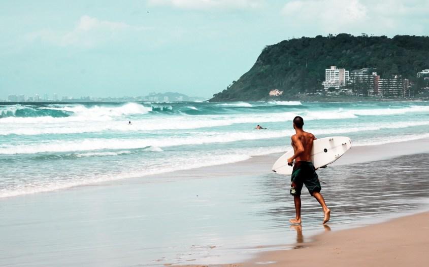 Gold Coast, Australia | Surffaaja juoksee mereen surffilauta kainalossa.