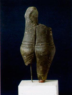 Оштетена женска фигура, чии украси на облеката се прикажани со врежани линии во водената глина