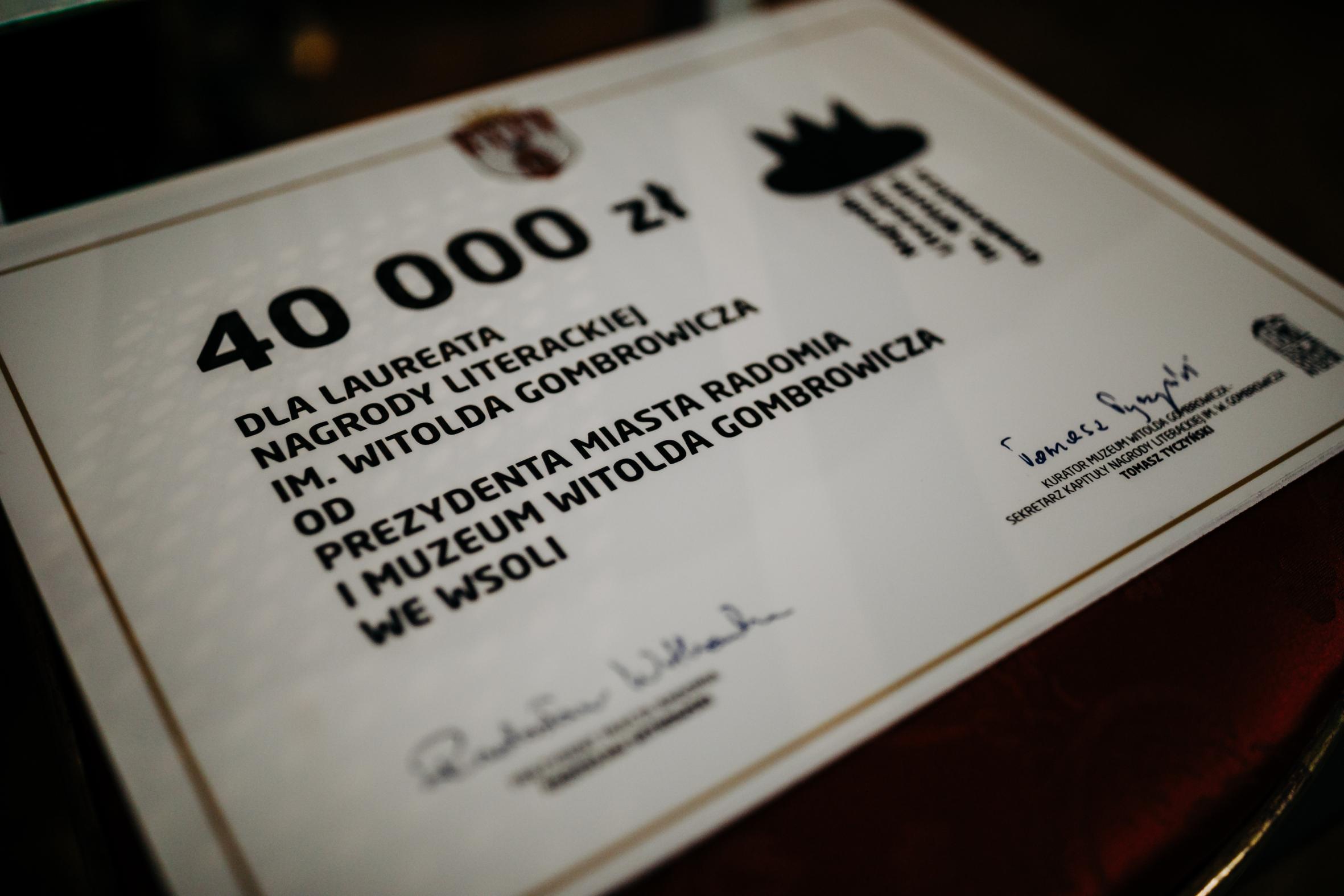 Na ciemnym tle w dużym zbliżeniu czek na czterdzieści tysięcy złotych dla laureata Nagrody Gombrowicza