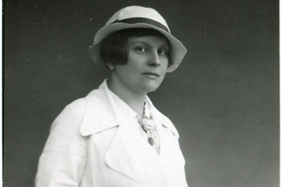 kobieta w średnim wieku, ubrana na biało. prawą rękę schowaną ma do kieszeni, na głowie kapelusz