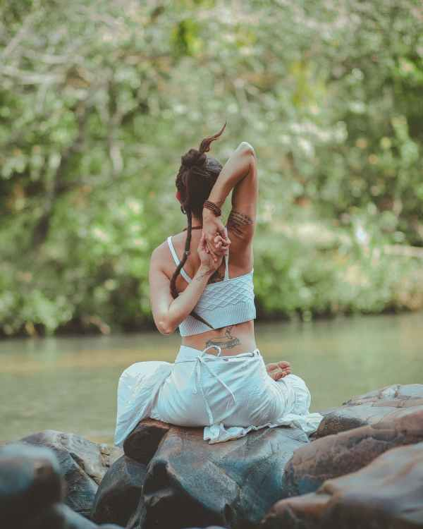 back view photo of a woman sitting near body of water doing yoga