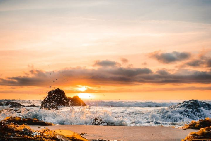 ocean smashed to sand during golden hour