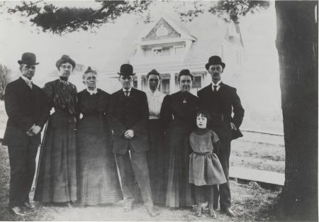 Photo of Keyes family standing next to big pine tree