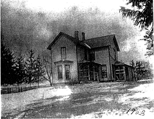Black and white photo of a farmhouse built in the traditional American style in the 19th century