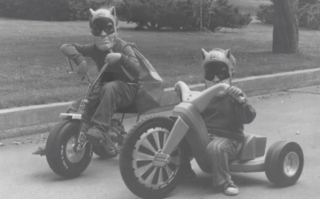 Photo of two boys riding their Big Wheels dressed as superheroes, 1970s
