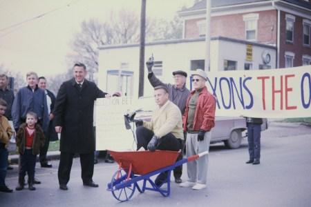 Photo of Doc Sauter sitting in a wheelbarrow