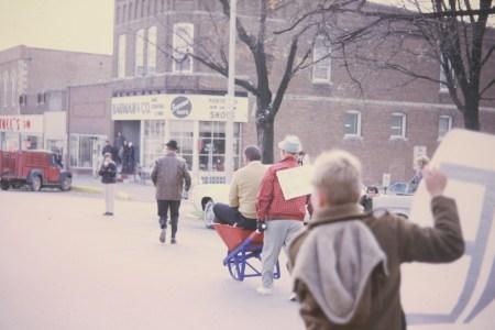 Photo of Paul Scott pushing Doc Sautter in wheelbarrow