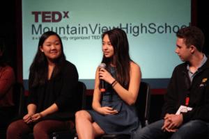 Naya Chang, Katherine Shok, and Zachary Hinz address the audience during the student