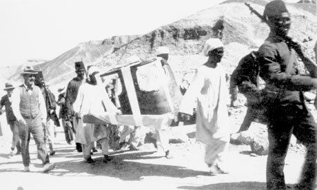 Carter, left, escorts a sarcophagus from the site. 1922.