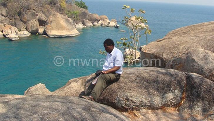 A tourist feels the cool breeze from Lake Malawi National Park section, a world heritage centre