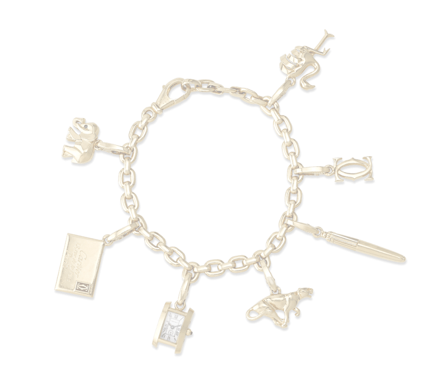 A gold bracelet with 7 charms on it including a book, a watch, and others