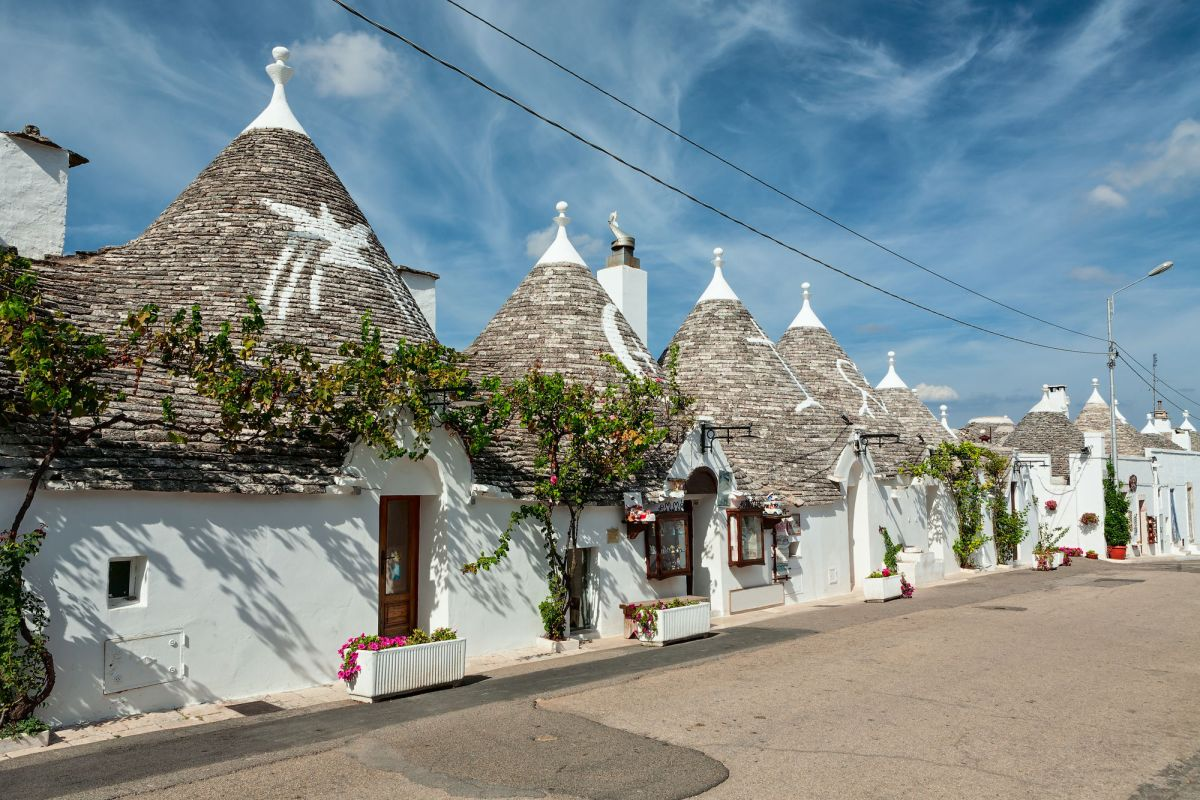 Trulli Houses In The Shopping Street In Alberobello Under A Blue Sky Puglia Italy