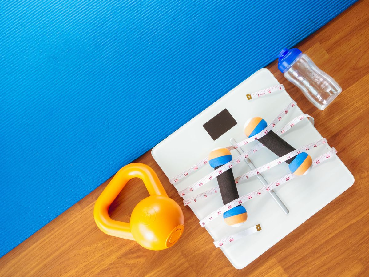 Weight Loss And Physical Activity Concept From Weight Scale Digital With Measure Tape For Check Body Shape And Workout Equipment On A Wooden Floor