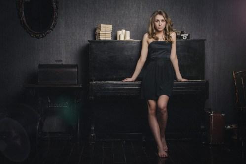 Девушка в черном платье у пианино в фотостудии