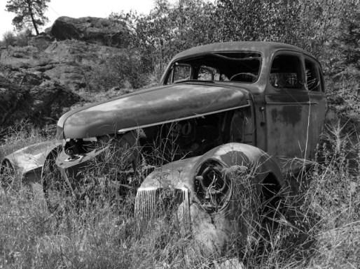 stock-photo-car-transportation-black-and-white-overgrown-abandoned-old-antique-vintage-rusting-d936de9d-2437-476c-903e-2f1a7b8b58da