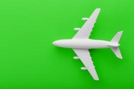 white-passenger-model-airplane-bright-green-background_94046-2759