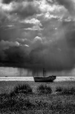 A wooden fishing boat sits on the beach at Aldeburgh on the Suffolk coast as a sudden summer squall passes by out to sea. A dramatic and atmospheric black and white fine art photographic print by Lee Thornberry. Suffolk fine art landscape photography. Greenman Photography.