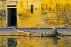 Woman waiting in boat by riverside, Hoi An Centre, Vietnam